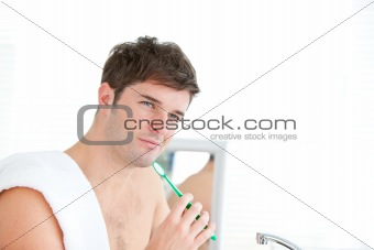 smart young male brushing his tooth with towel on his shoulder