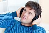 attractive young man listening music sitting in the living-room