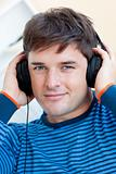 peaceful man listening music using headphones smiling at the cam
