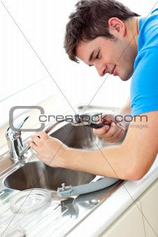 Caucasian man repairing a kitchen sink at home