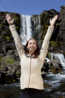 Beautiful Young Woman Celebrating Arms Raise By A Waterfall