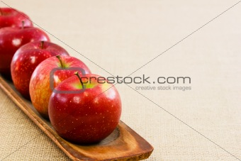 Five fresh red apples lined up on a wooden tray