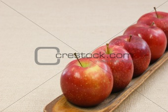 Five crisp red apples in a row