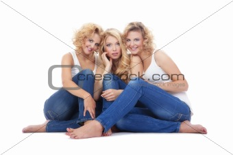 three young women sitting on the floor, looking - isolated on white