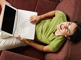 woman with pc laughing on sofa