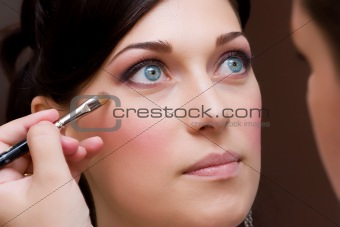 make up artist makeing a colour correction with an brush