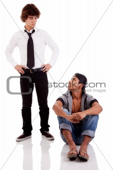 two men of different ethnicity, one sitting looking at the other standing, isolated on white, studio shot