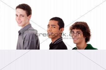 three young, of different colors man holding a white board, looking to camera, isolated on a white background