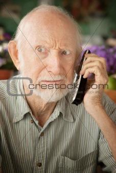 Grumpy senior man on telephone