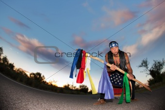 Indigenous man in the middle of a road with ceremonial pole and