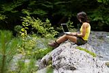 Girl with a laptop, sitting on a rock