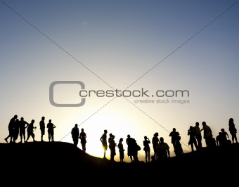 Group of people silhouetted against the sun on top of a mountain