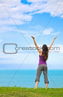 A beautiful young woman standing with her arms up in the air loo