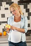 Pregnant woman peeling an apple