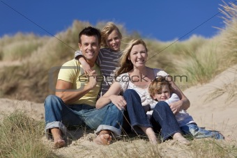 Mother, Father and Two Boys Sitting Having Fun At Beach