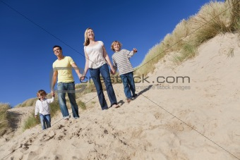 Mother, Father and Two Boys Walking Having Fun At Beach