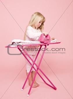 Little girl ironing dress