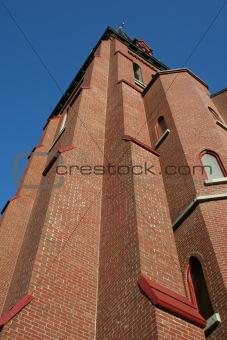 towering brick church steeple against blue sky