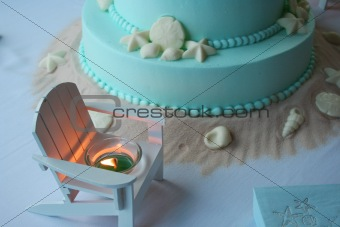 Beach themed wedding cake with lit candle