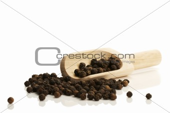 black peppercorns with a small wooden shovel side