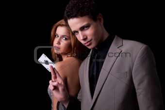 young couple, man holding a ace of spades, isolated on black, studio shot