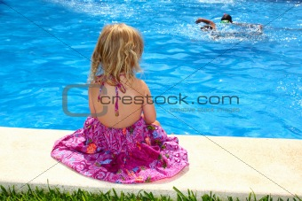 Little blond girl sitting rear back swimming pool