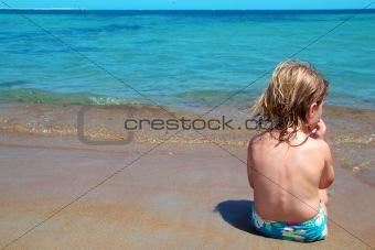Little blond girl sit in beach shore looking ocean