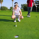golf young woman looking and aiming the hole