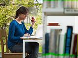 girl holding apple in library
