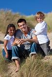 Father, Son &amp; Mixed Race Daughter Sitting on Beach