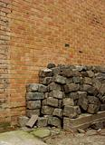 large stack of cobbles in front of a brick wall