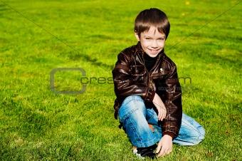 Little boy sitting on the grass