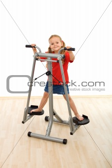 Little girl playing on stretcher device in the gym