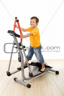 Smiling boy on elliptical trainer in the gym
