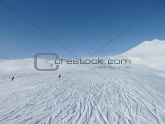 Skiers on wide open piste in French alps