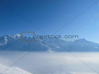 Mountain peaks rise above the clouds with bright blue sky