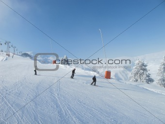 Skiers on wide ski slope on sunny day
