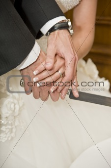 Detail of bride and groom cutting wedding cake