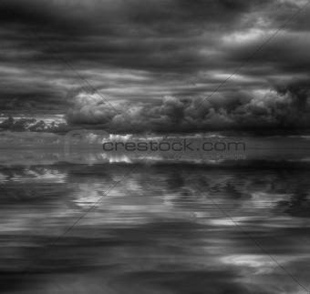 Beautiful water reflection of evokative cloudscape in monochrome