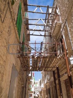 Alley in Molfetta Oldtown with reinforced scaffolding. Apulia.