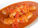 Sausages in tomato sauce on white dish.