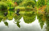 Oriental bronze heron sculptures in Autumn Fall lake setting