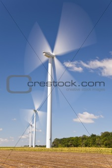 Green Energy Wind Turbines In Field of Sunflowers