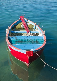 Coloured rowboat in clear sea.