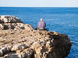 Fisherman sitting on the rocks.