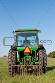 Green Tractor in a Farm Field with Blue Sky