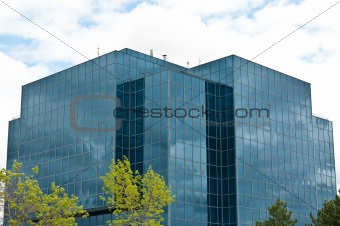 Modern Office Building with Trees and Clouds