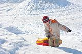 Boy drags red-yellow tube on a snow