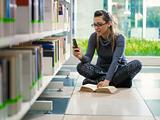 girl text messaging with phone in library