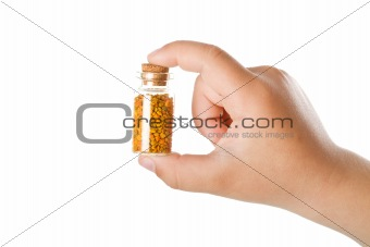 Small bottle with pollen in child hand